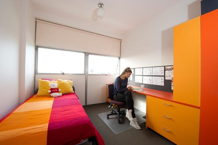 UniLodge-@-Melbourne-Single-Studio-View-Door-to-Window-Student-at-Study-Desk